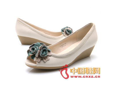 Lightweight mid-heeled wedge design with romantic flowers clustered around toe cap