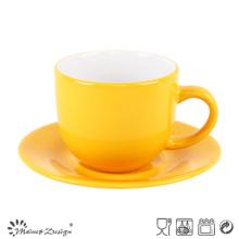 Taza y platillo de glaseado amarillo brillante