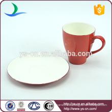 Delicada taza de café rojo y soportes de platillo