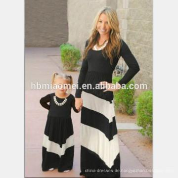 Die passende Kleidung der neuen Designmuttertochter, die passende Kleidung der Familienkleidung für Mutter und Kinder ankleidet, kleiden an