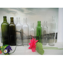 Vaciar diferentes formas y botellas de vidrio de diferentes colores para el aceite de oliva