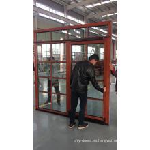Puerta abatible y corredera con barras coloniales de aluminio corredera con revestimiento de roble. Puerta corredera de vidrio con rejas.