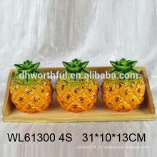 Condimento cerâmico barato definido na forma de abacaxi com fundo de madeira
