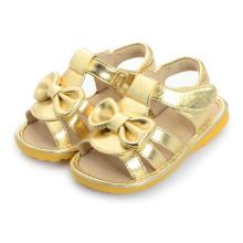 Sandálias de bebê de ouro com arco lindo