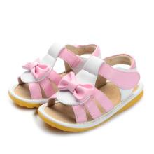 Sandálias de bebê cor-de-rosa com uma curva linda