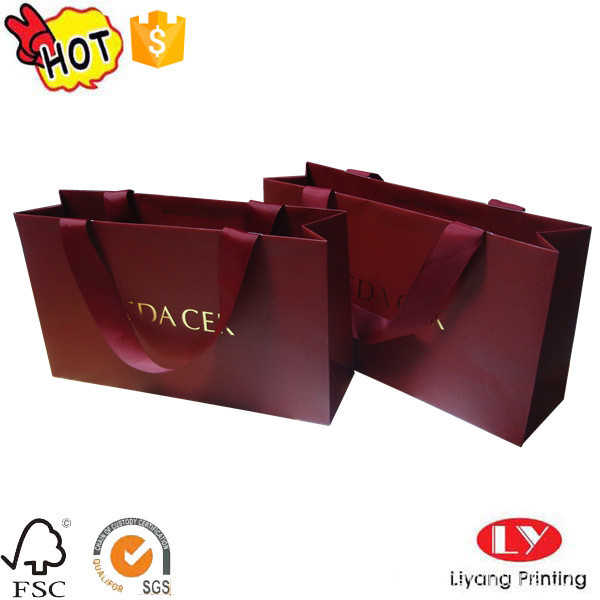 Shopping bag di carta alla moda con manico a nastro