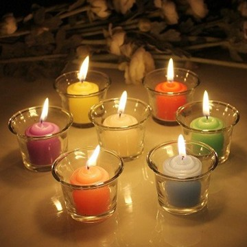 Multi-colored pillar votive candle in glass jar