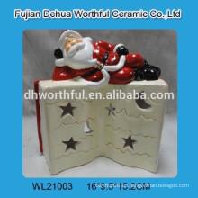 Santa encantadora con libro de cerámica llevó la luz de Navidad