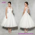 El vestido de novia estilo té de longitud vintage con cuello de ilusión embellecido con encaje le da a esta línea clásica una actualización moderna