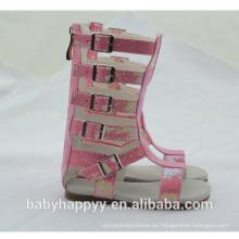 La última manera embroma las sandalias del gladiador de la rodilla del color de rosa de la muchacha alta