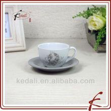 Keramische weiße Tasse und Untertasse mit Abziehbild darauf
