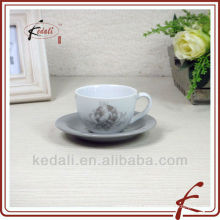 Ceramic white cup and saucer with decal on it