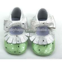 Las muchachas hermosas calzan los zapatos de bebé brillantes del arco lindo de los moccasins del niño