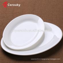 Le restaurant de l'hôtel utilise une assiette de dessert ovale en céramique blanche