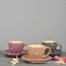Copo de café com design pontilhado e café com pires