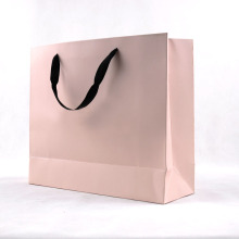Elegante bolso de compras de papel rosa con mango