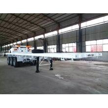 Camion semi-remorque porte-conteneur transportant un lit plat