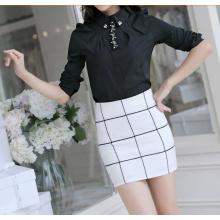 Women's black dress shirt on skirt