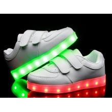 Weiße Kinder arbeiten leuchtende LED-Schuhe an