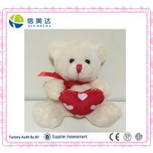 Белый плюшевый мишка с красным сердцем