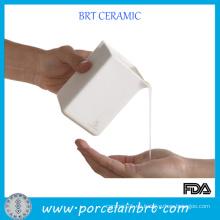Envase de cerámica blanca de la vela del masaje