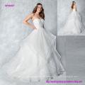 Haga una entrada en este vestido de novia sin tirantes de organza con faldas y botones abajo de la parte posterior