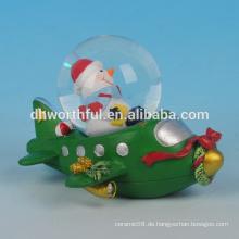 Weihnachten Dekoration Harz Weihnachten Schneekugel mit Schneemann Figürchen im Flugzeug