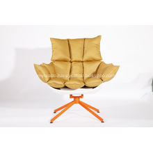white husk chair with orange seat cushion