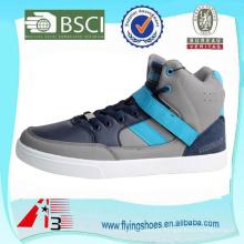 Homens novos olham os calçados superiores do skate da parte superior