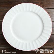 Porcelana blanca en relieve con plato de cena de borde rojo