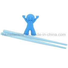 Niños entrenando palillos con ayuda
