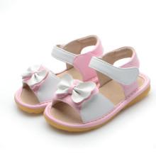 Sandálias brancas do bebé com um arco bonito