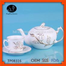 Olla de cerámica blanca con reborde de oro, tetera en relieve innovadora con taza y platillo, tetera de cerámica con diseño de flores
