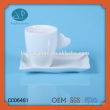 Taza y platillo de cerámica blanca estupenda, taza y platillo de cerámica con la galleta, taza de té con la manija del corazón