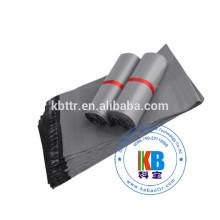 El mensajero polivinílico blanco viste los bolsos plásticos grises del anuncio publicitario del bolso del envío
