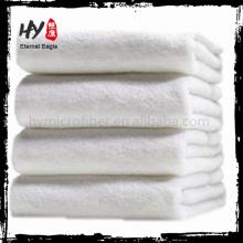 Feuilles blanches de serviette de bain toutes neuves, serviette compressée de ligne aérienne d'hôtel, serviette de mongram de coton