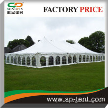 12x24m pole tent with windows and sides secured to grass ground by pegs and guy ropes