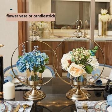 Vaso de flores com castiçal de metal dourado decora a casa