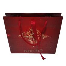 Saco de compras de papel com fita vermelha