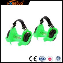 Resplandor caliente de las ventas en el patín de ruedas oscuro que destella dos zapatos de las ruedas