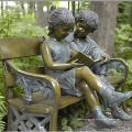 bronce niño y niña sentada en la escultura de banco