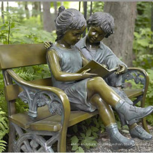 Bronzejunge und -mädchen, die auf Bankskulptur sitzen