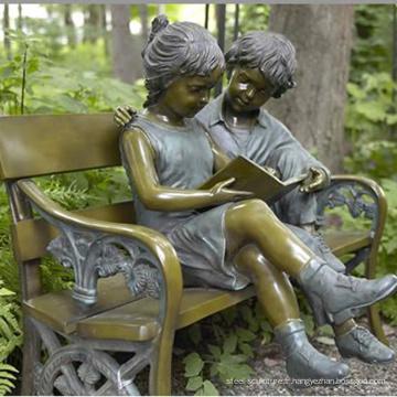 garçon et fille de bronze assis sur une sculpture de banc