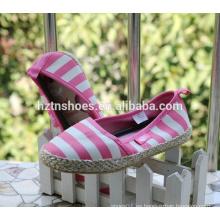 Los zapatos ocasionales de las muchachas rosadas rayaron los zapatos de la albaricoque de la lona