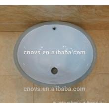 Debajo del fregadero de cerámica del lavabo contrario del contador