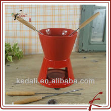 red stoneware fondue set with fork