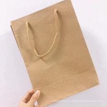 Обрабатывает коричневый пакет из крафт-бумаги с напечатанным логотипом