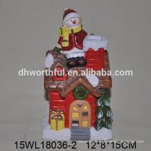 Artistic craft ceramic snowman figurine sitting on the house