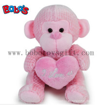 Venta al por mayor China divertida rosa monkey peluche con almohadilla de corazón rosa