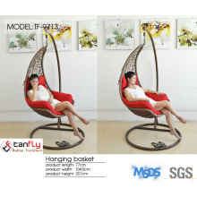 Hanging wicker pod swing chair with full cushion.
